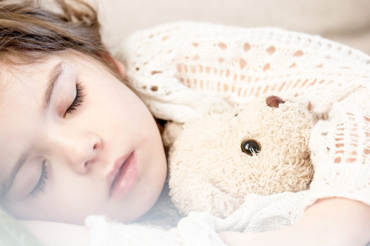 Girl sleeping with cuddly toy