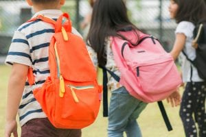 Young students wearing backpacks