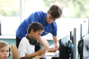 Tutor helping student on computer