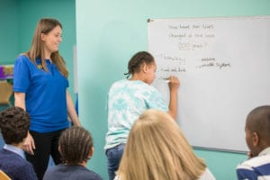 teachers answer questions on schools safety - girl writing on a whiteboard in class