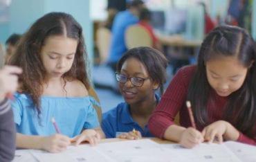 Explore tutors helping children in the classroom