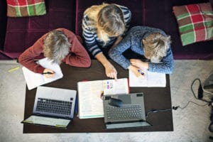 two students get home schooling help from parent
