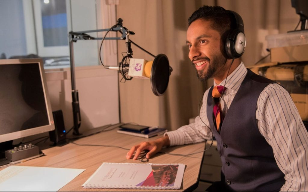 Presenter and maths advocate, Bobby Seagull sat at a desk recording audio on a microphone.