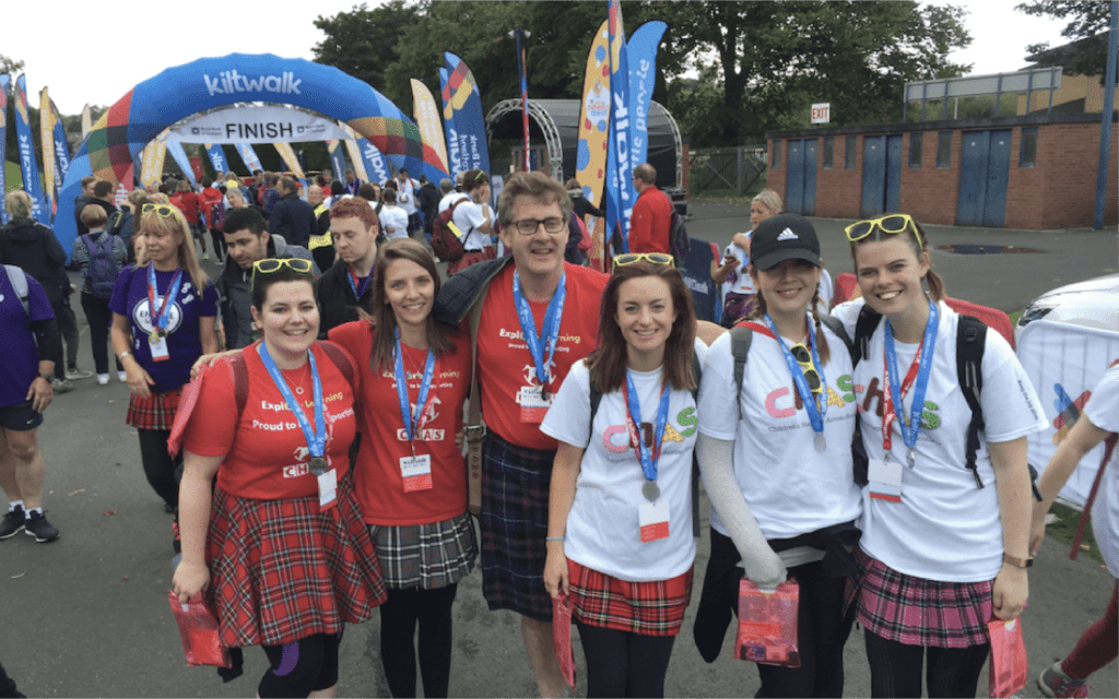 Members of the Explore Learning team taking part in a charity event all wearing Scottish kilts.