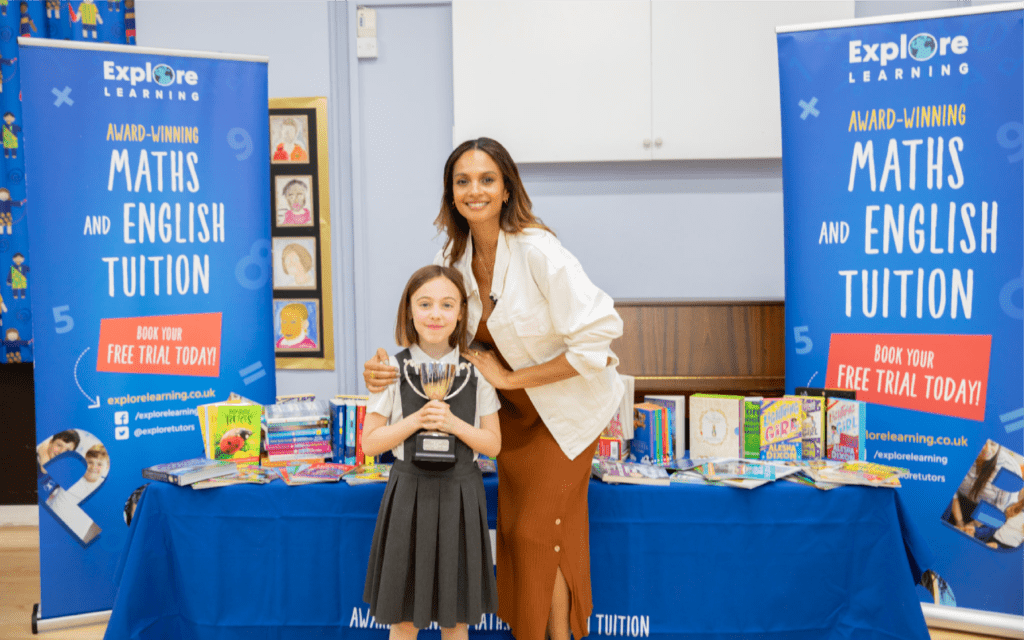 Alesha Dixon standing with the winner of the 2018 Explore Learning Writers' Awards in front of a table full of books for the child's school.
