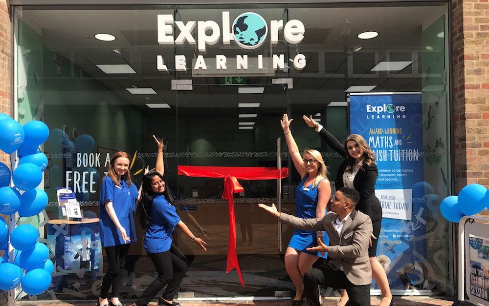 Explore Learning staff celebrating the opening of a new learning centre with a large red ribbon cutting and balloons.