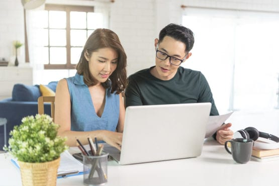 asian couple looking at a laptop to find tutoring in a brightly lit room