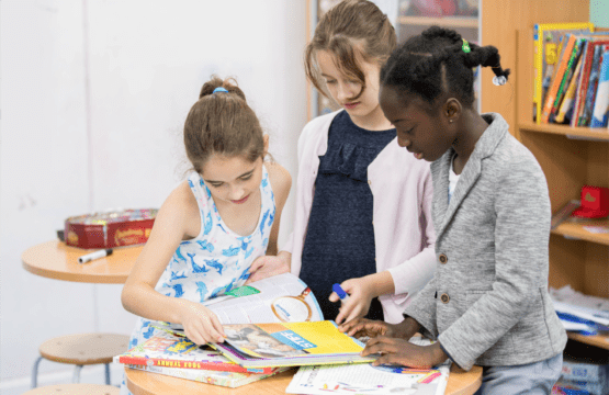3 young girls discover more standing around a table looking at books together.