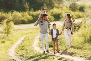Family walking in a field in the summer time