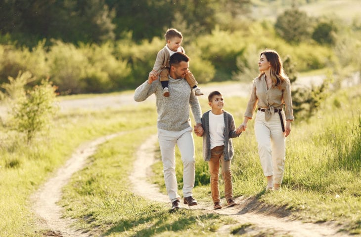 Family walking together in a field in the summer time