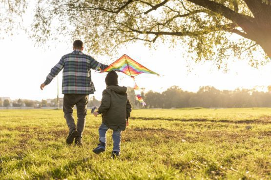 Parent and child playing with kite in a field during summer