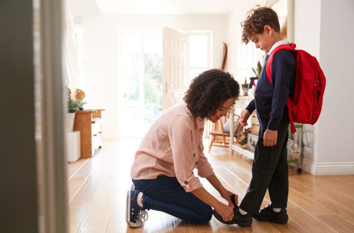 Mother helping boy get ready for the first day back to school